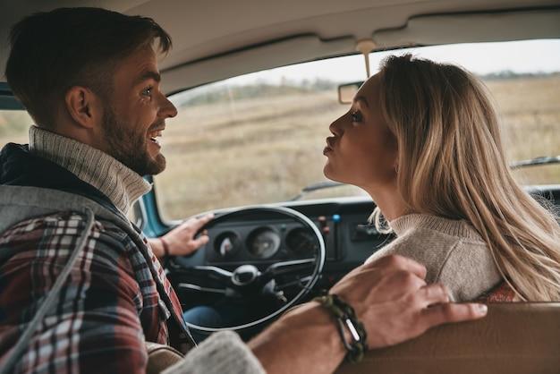 Amare tutto di lei. giocosa giovane donna che fa una smorfia mentre è seduta sul sedile del passeggero anteriore in un mini van in stile retrò con il suo fidanzato