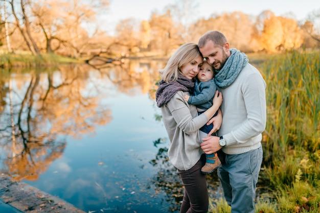 La coppia amorosa della famiglia abbraccia il loro bambino alla natura con il lago