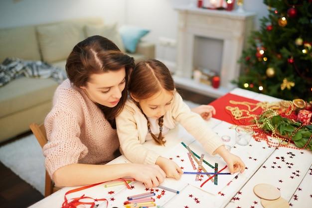 Famiglia amorosa che fa la decorazione di natale