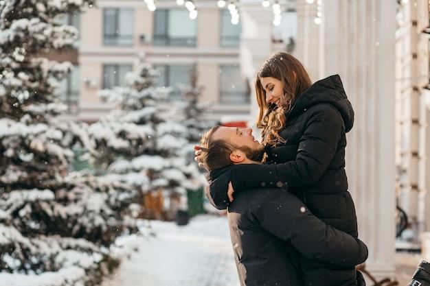 Un uomo amorevole e felice che tiene la sua ragazza tra le braccia