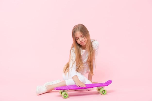 Amare il suo penny board. bambina che mette mano sul ponte di bordo su sfondo rosa. adorabile pattinatrice piccola con penny board viola. esecuzione di acrobazie con lo skateboard.