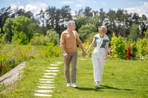 Coppia di sposi innamorati che passeggiano in campagna