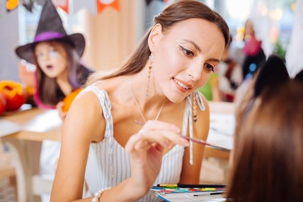Madre amorevole. madre amorevole premurosa che si sente attenta mentre dipinge il viso della sua piccola figlia per la festa di halloween
