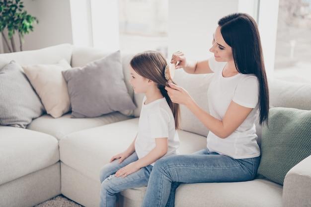 Madre amorevole pettina i capelli del bambino in casa al chiuso