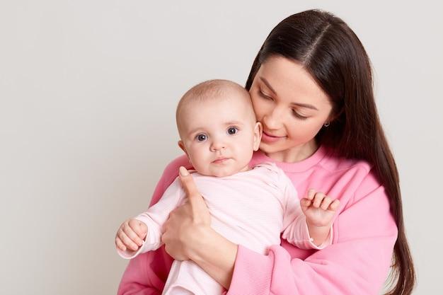 Madre amorevole che tiene e abbraccia il bambino nelle sue mani, donna con i capelli scuri che indossa un maglione rosa casual guardando sua figlia, in posa isolata sopra il muro bianco.