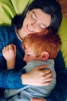 Madre amorevole che abbraccia il figlio giocoso. concetto di infanzia. donna single che gioca con il suo bambino a casa. stile di vita familiare all'interno della casa con i bambini. animazione per bambini piccoli al chiuso.