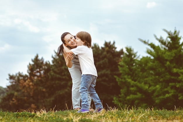 Madre amorevole che bacia il suo giovane figlio attraente sulla guancia. immagine tonica