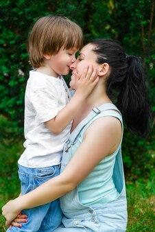 Madre amorevole che bacia il suo giovane figlio attraente sulla guancia