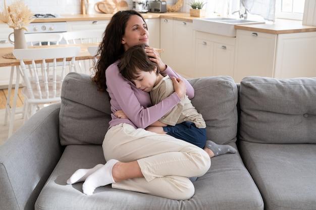 Amorevole madre genitore abbraccia piccolo figlio esprimendo tenerezza amorevole mamma conforto bambino abbracciando