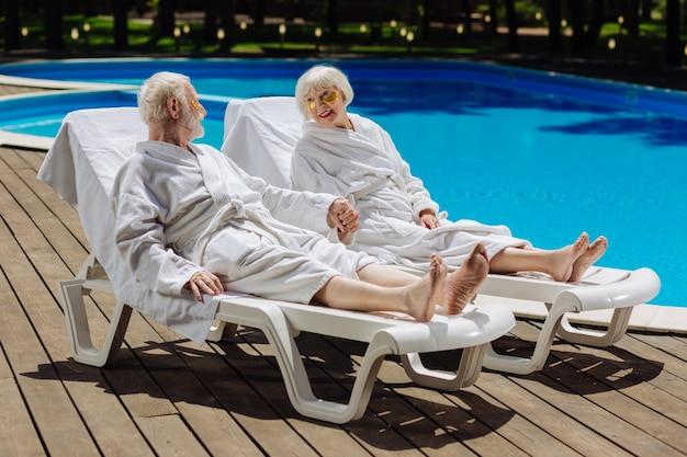 Amorevole uomo in pensione che tiene la mano della sua bella moglie mentre trascorre il fine settimana vicino alla piscina