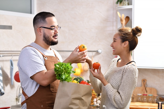 Giovani coppie asiatiche amorose che cucinano nella cucina che produce alimento sano e che tengono insieme il sacchetto della spesa della drogheria con le verdure che si divertono