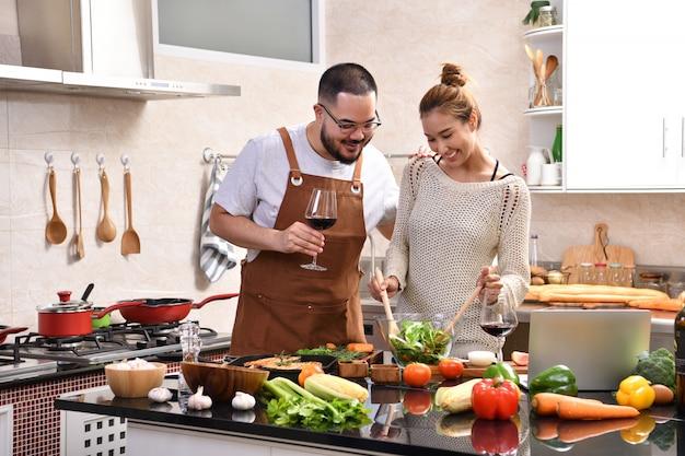 Giovani coppie asiatiche amorose che cucinano nella cucina che produce insieme alimento sano e che bevono vino