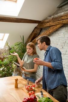 Giovani coppie amorose che tagliano insieme le verdure in cucina rustica e che esaminano ricetta la compressa digitale