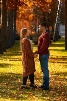 Giovani coppie amorose risalenti in autunno in piedi mano nella mano in un parco con foglie colorate sul terreno e alberi che si guardano negli occhi