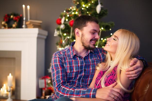 Amorevole giovane coppia abbracci seduto sul tappeto di pelliccia