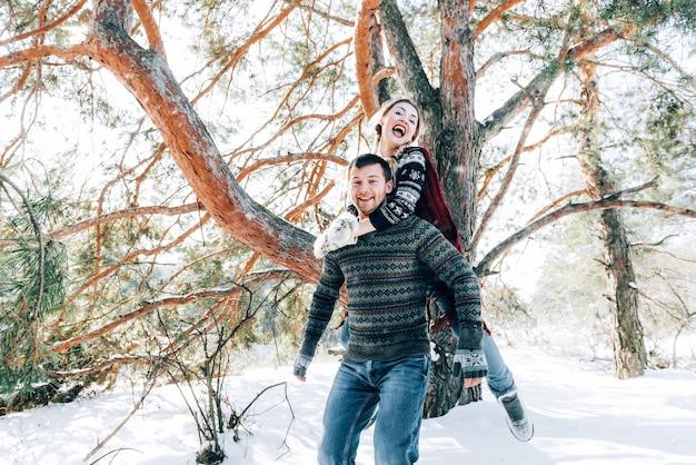 Una giovane coppia amorevole sta riposando in montagna in una foresta innevata. concetto di riposo articolare