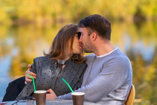 Amare la giovane coppia baci e coccole in un ristorante all'aperto che si affaccia su un lago