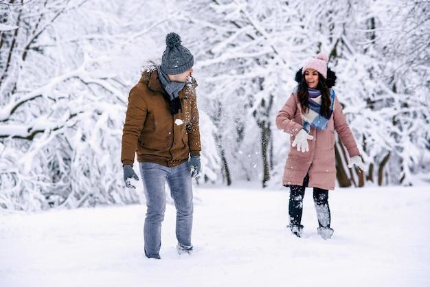 Giovani coppie amorose che giocano con le palle di neve in un parco d'inverno