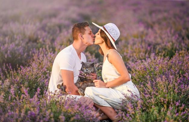 Amare la giovane coppia che si rilassa in un campo di lavanda e si bacia.