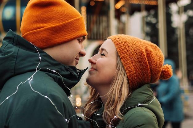 Giovani coppie amorose che stanno insieme all'aperto fra le ghirlande alla stagione invernale