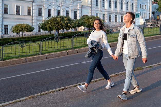 Amare la giovane coppia che cammina per la città tenendosi per mano.