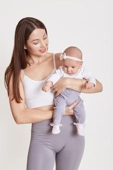La giovane madre europea amorevole tiene il piccolo bambino neonato, godendo del momento insieme, la mamma premurosa abbraccia il piccolo bambino del bambino, la maternità, l'assistenza all'infanzia, isolata sopra fondo bianco.