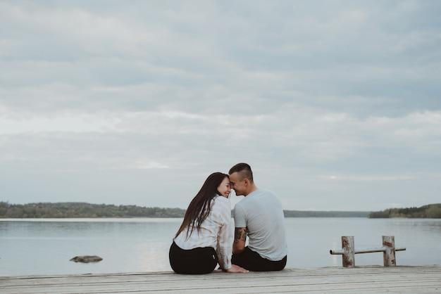 Giovani coppie felici amorose che abbracciano sulla spiaggia in riva al fiume durante il giorno