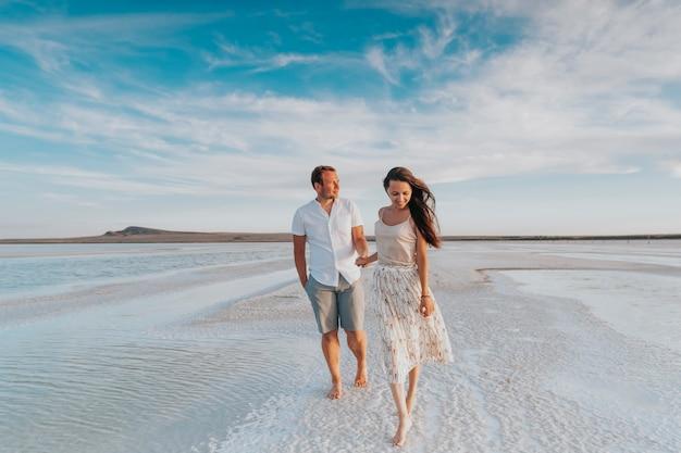 Una giovane coppia sposata amorevole cammina lungo la riva del mare. sposi in viaggio di nozze.