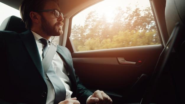 Basso angolo di uomo d'affari in abito classico che viaggia in auto sul sedile posteriore guardando fuori dalla finestra