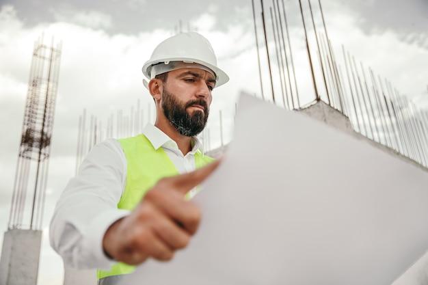 Basso angolo di ingegnere maschio barbuto adulto concentrato in elmetto protettivo e panciotto in piedi sul cantiere ed esaminando il progetto