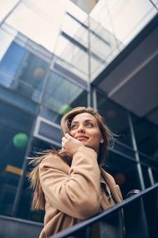 Angolo basso di una donna bionda sognante con il mento appoggiato sulla mano che guarda lontano