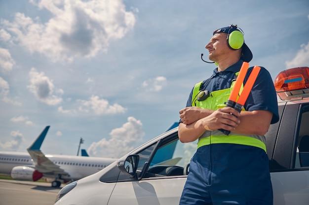 Angolo basso di un lavoratore aeroportuale caucasico concentrato con bacchette di smistamento che fissano in lontananza