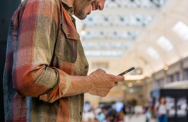 Uomo di angolo basso che per mezzo dello smartphone