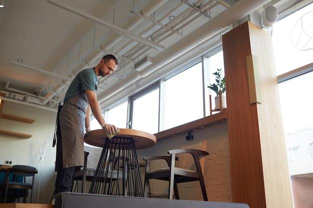 Ritratto ad angolo basso dei tavoli di pulizia del cameriere maschio in bar o caffetteria mentre si prepara per l'apertura al mattino, copia spazio