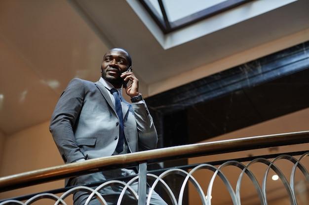 Ritratto ad angolo basso di un uomo d'affari afroamericano di successo che parla tramite smartphone mentre si trova sulle scale in un hotel di lusso, copia spazio