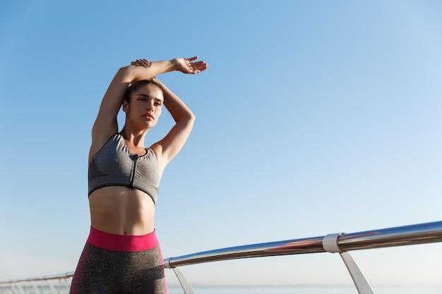 Inquadratura dal basso della donna attraente in forma in reggiseno sportivo e leggings