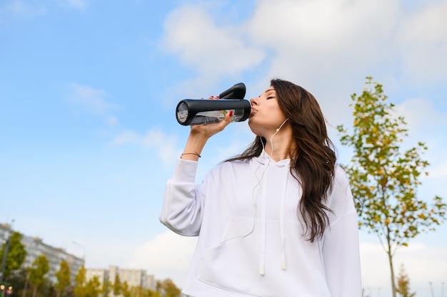 Inquadratura dal basso di una ragazza attraente in felpa bianca e cuffie che tengono la bottiglia e bevono acqua dopo l'allenamento, lo stretching, il fitness all'aperto