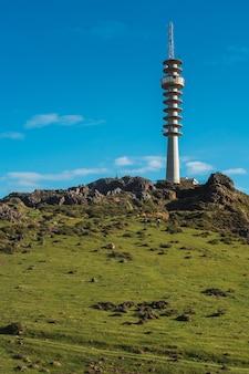 Inquadratura dal basso di una torre di osservazione di forma insolita su una collina
