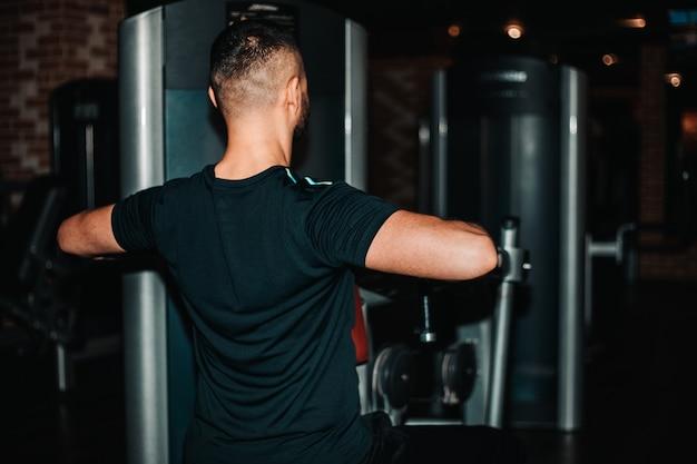 Colpo ad angolo basso di un uomo atletico muscoloso e tonico, forte e giovane, che fa esercizio usando una macchina crossover in palestra. concetto di forza motivazione fitness sport.