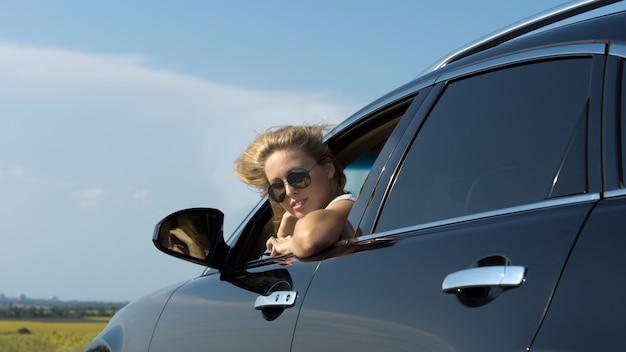 Inquadratura dal basso di una donna bionda in occhiali da sole guardando indietro dal finestrino di una macchina