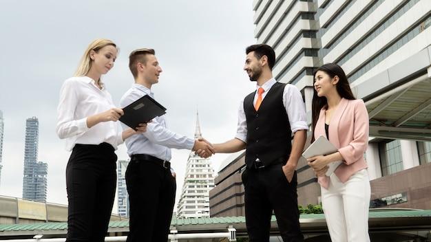 Punto di vista di angolo basso dei colleghi di affari che discutono mentre stando nella città