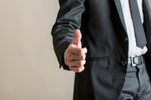 La vista di angolo basso dell'uomo d'affari che mostra pollici aumenta il segno