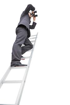 Punto di vista di angolo basso dell'uomo d'affari che sta sulla scala facendo uso del binocolo
