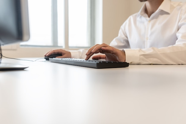 Inquadratura dal basso di un uomo d'affari in camicia bianca che digita sulla tastiera di un computer.