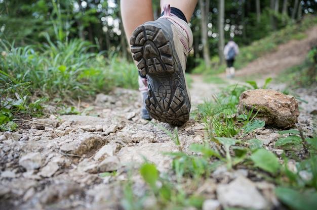 Inquadratura dal basso del piede femminile che cammina sul sentiero di montagna