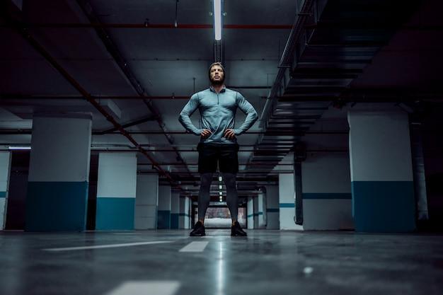 Inquadratura dal basso dello sportivo caucasico bello in forma in abbigliamento attivo in piedi nel garage sotterraneo con le mani sui fianchi. concetto di vita urbana.