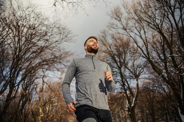 Inquadratura dal basso dello sportivo in forma che fa jogging nella natura al giorno d'inverno nevoso. freddo, fitness invernale, esercizi cardio