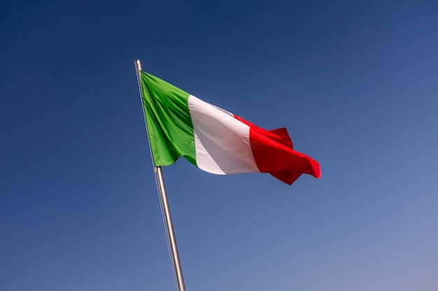 Inquadratura dal basso della bandiera dell'italia che ondeggia contro il cielo blu chiaro