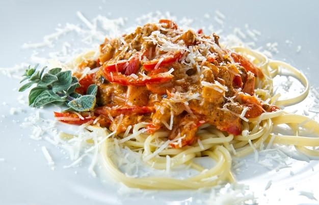 Vista dal basso di una porzione di spaghetti italiani con un ragù alla bolognese o bolognese a base di carne su un piatto bianco semplice