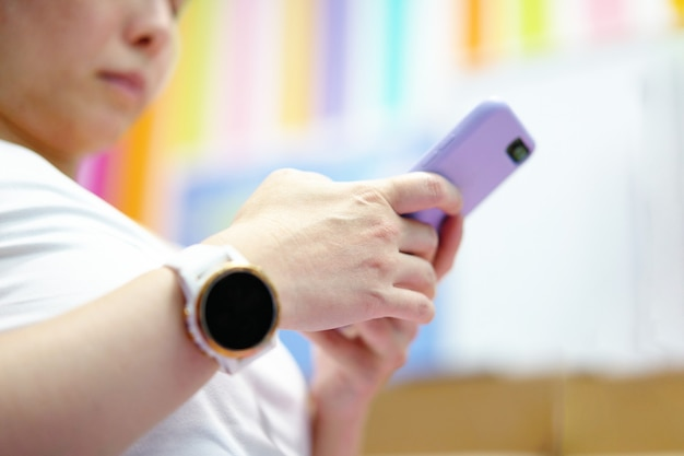 Vista ad angolo basso della donna che indossa abbigliamento sportivo si siede e usa lo smartphone dopo l'esercizio aerobico indoor a casa con spazio per le copie